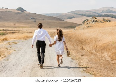 Road. Mountains. Couple   holding hands and running away in mountains. Woman and man in love walking outdoors. Love Story