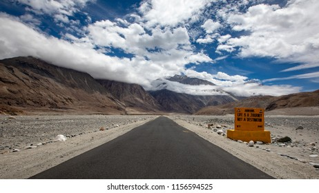Road in mountains Himalayas and dramatic clouds on blue sky. Leh - Ladakh, Jammu and Kashmir, India