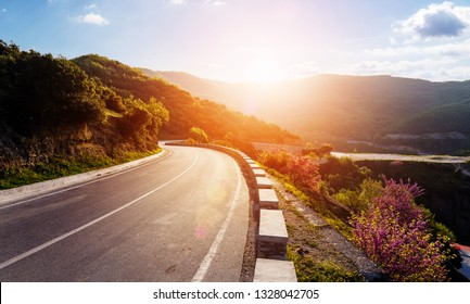 Road in mountains. Kalabaka region. Meteora. Greece. Empty asphalt road with glowing perfect sky and sunlight. Landscape with beautiful winding mountain road with a perfect asphalt in the evening.