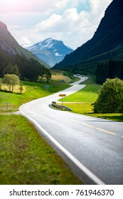Road in mountains of Norway, Europe. Auto travel through scandinavia. Blue cloudy sky in background. White house in foreground.