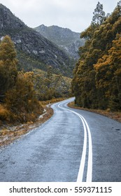 Road and mountains out in the Tasmanian country during winter on a rainy day.