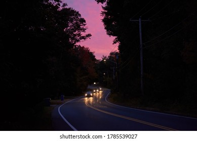 Road with moving cars at dusk, trees along it, sunset sky on the background in Massachusetts, USA