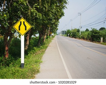 Road narrows traffic sign with country road.