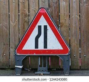 Road Narrows Traffic Sign Warning at Fence