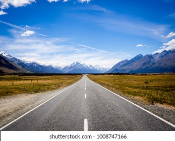 The Road to New Zealand - Snow Capped Mountains Mt Cook Highway Surrounded by Grass Land Straight Road Blue Cloud Sky in The Middle of the Road