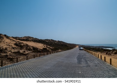 A road next to a beach and ocean in Portugal