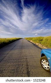 Road to nowhere. A car about to runaway on an old road, over the blue sky