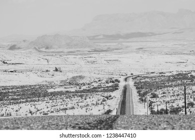 A road offers a steep decline into distant layers of sand.