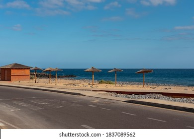 Road with old pedestrian crossing towards a golden manmade sand beach near the Atlantic with straw umbrellas or palapas and a chiringuito, deserted coast in San Blas, Tenerife, Canary Islands, Spain