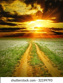 Road on field over sunset
