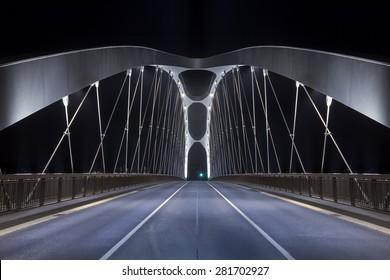 Road on modern frame bridge illuminated at night