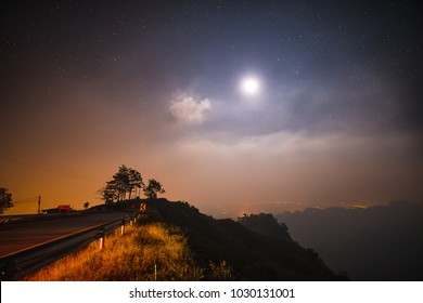 Road on the mountain at night with the stars and moon.
