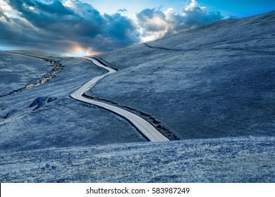 road on wasteland lead to sunrise