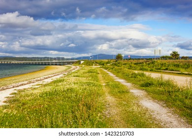 Road over the coastal dune of Bao beach in Arousa Island with the bridge at background