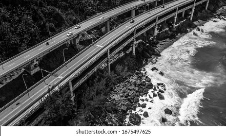 Road over the sea shore with cars crossing it and waves under it