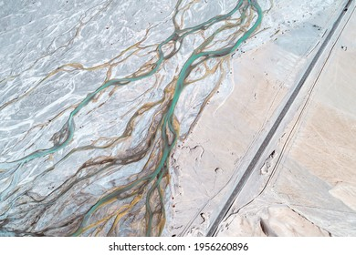 A road passing by a dry riverbed on the Qinghai-Tibet Plateau