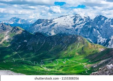The road in the Passo Pordoi valley and the  of Dolomites Alps, Passo Pordoi, Val Gardenna, South Tyrol, Dolomites, Italy.