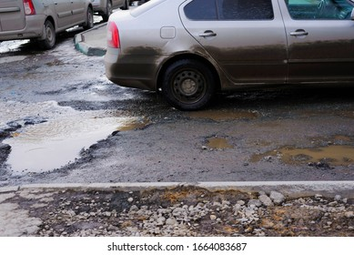Road pits in the city in the spring after the snow melts. Problem of roads and asphalt in the city.