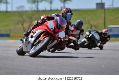 Road racing motorcykel in high speed into a curve, panning shot