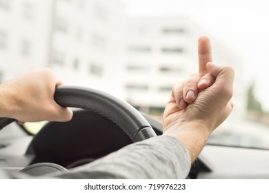 Road rage. Man driving and showing middle finger in car. Driver flipping the bird. Bad behavior and attitude in traffic.