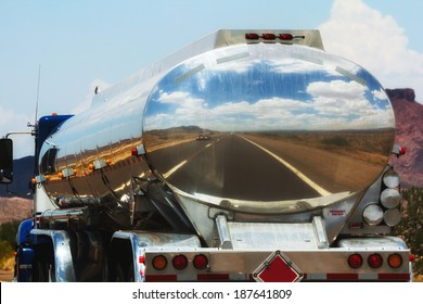 The road is reflecting in the fuel tanker of a truck