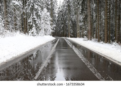 Road with reflection of snow covered trees in the Black Forest.