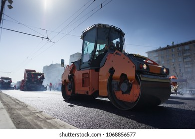 Road repair, compactor lays asphalt. A lot of heavy special machines