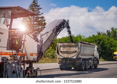 Road repair, highway reconstraction. Heavy special machines. Feeder, asphalt paver and pneumatic-tyred roller in operation. Side view. Closeup.