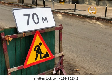 road repair sign on a wooden fence, The distance to the problem area is 70 meters. road maintenance. Protections an obstacle with information signs about repair work and the distance to the hole