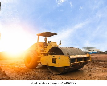 Road roller at road construction site with cloudy blue sky during sunset