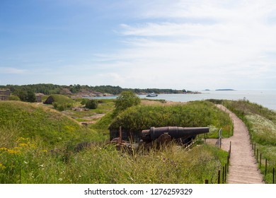 The road runs along the shore of the historic Suomenlinna fortress island near the old Russian cannons left over from ancient times. Suomenlinna, Finland.