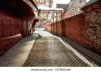 the road runs between a red marble house and a red brick wall on a sunny day