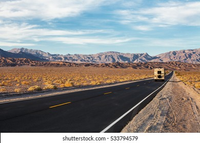 A road runs in the Death Valley National Park, California, USA. Motorhome on the road