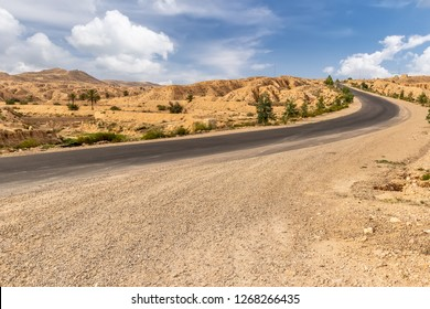 Road at Sahara desert in the afternoon with beautiful cloudy sky. Montain landscape. Tunisia.