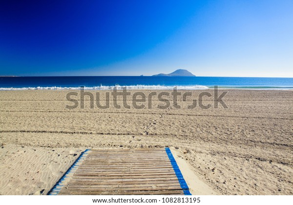 The road to the sandy beach, the blue sea and the island in Spain