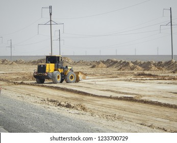 Road scraper in the steppe. Laying a new road in the desert.