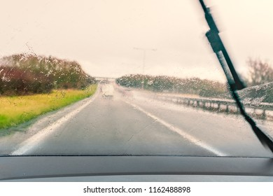 road seen through a wet windscreen whilst driving in the rain. One wiper can be seen moving across the windshield