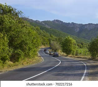Road serpentine on which three cars ride, against the background of mountains and green trees