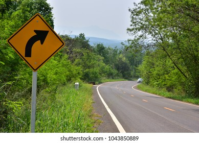 road sharp curves sign in country side middle forest in Thailand.