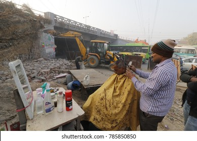 A road side barber works at a construction site, where expressway construction taking place to widen Meerut - Delhi expressway on December 22, 2017 in New Delhi, India.