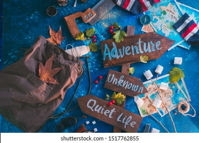 Road sign with Adventure, Unknown and Quiet Life directions. Travel essentials creative header with socks, maps, and marshmallows, wanderlust concept