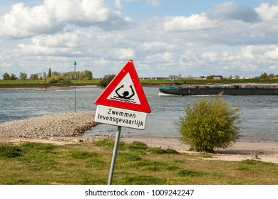 Road sign along the Waal river: dangerous swimming (in Dutch) and risk of drowning; a passing cargo ship well illustrates the real danger.