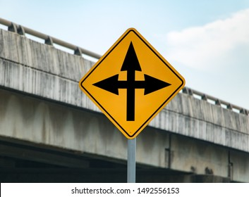 Road sign with arrows informs about crossing on the road. Warning of junction with change course.