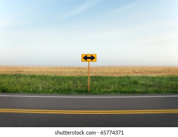 A road sign with arrows pointing in two directions along a quiet country road.