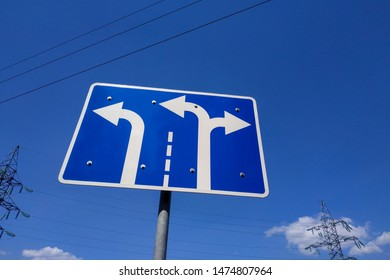 The road sign is blue with white arrows indicating the direction of movement along the lanes and the number of lanes. Traffic sign on the side of the roadway.