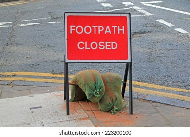 Road sign for a closed footpath held down by sandbags