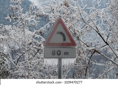 Road sign danger curve covered in ice after the freezing rain