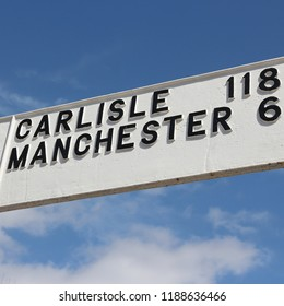 Road sign in England: directions to Carlisle and Manchester. Distances in miles.