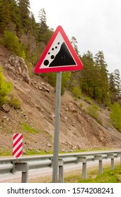"""Road sign - Falling rocks. Road sign """"Falling rocks"""" on the background of a mountain road and a rocky slope. Hazard road sign"""