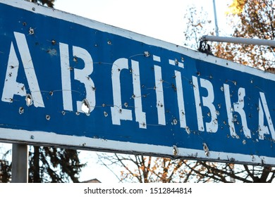 """Road sign with the inscription in Ukrainian - """"Avdiivka"""",town of Donetsk region, broken by bullets during the war in the Donbass, Ukraine. Armed conflict east of Ukraine, destruction"""